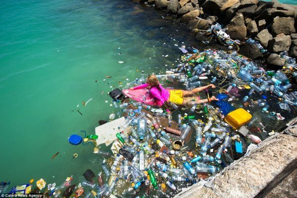 swimming at sea with plastic bottle pollution